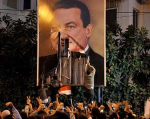 Egypt protests: Demonstrators deface a poster of Egyptian President Hosni Mubarak