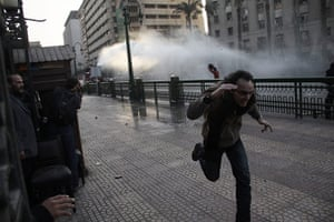 Egypt protests: A man runs from a police water cannon in Cairo