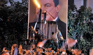 Egyptian protesters tear down a poster of Egypt's President Hosni Mubarak, Egypt