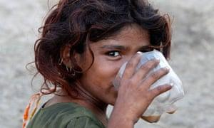 Pakistani flood victim Hooran, six, drinks tea in a Sindh relief camp