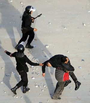 Egypt Protests: Police officers carry an injured colleague in Suez