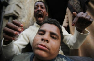 Egypt Protests: An anti-government protester reacts as his relative is injured