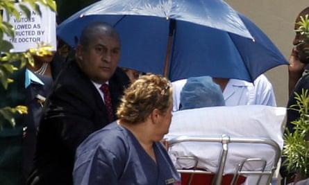 Former South African president Nelson Mandela (under umbrella) leaves hospital in Johannesburg