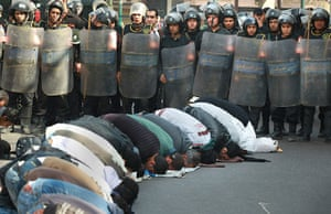 Egypt Protests: Locals pray in the street watched by riot police
