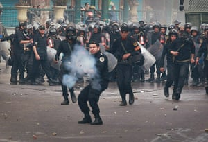 Egypt Protests: A riot policeman fires tear gas at protestors in Cairo