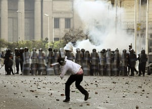 Protests in Egypt: An Egyptian protester throws stones towards a line of riot police