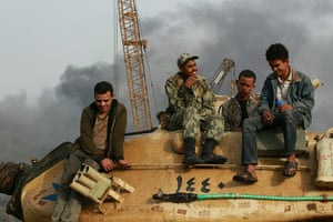 Egypt 29 January: People sit on an army tank in Tahrir Square in Cairo