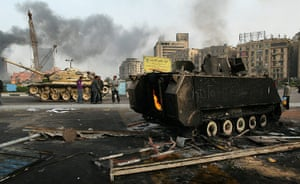 Egypt 29 January: An army tank and a burnt out armoured personnel carrier in Tahrir Square
