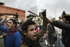 Egypt 29 January: Egyptian demonstrators chant slogans in front of army tanks in Cairo