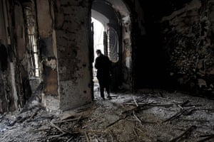Egypt 29/01: An Egyptian man surveys the fire damage at a burned police station