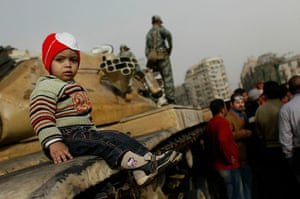 Egypt 29/01: A child sits on a tank while an Egyptian soldier stands by