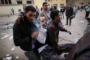 Egypt 29/01: Protestors carry an injured man during clashes with riot police in Cairo