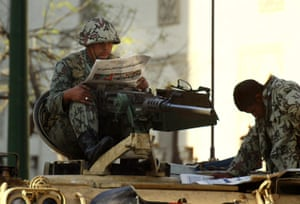 egypt protests continue: Egyptian army soldiers read newspapers