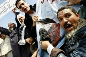egypt protests continue: An Egyptian demonstrator hits Mubarak portrait with a shoe