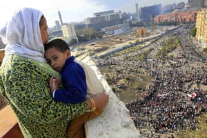 Egypt protests: A mother and child watch protesters gather at Tahrir square in Cairo
