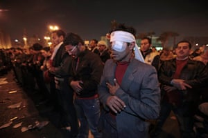 Egypt uprising: A wounded protester prays in Tahrir square