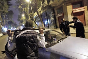 Egypt uprising: Egyptians keep watch and control cars in a street in central Cairo