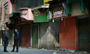 Local men stand next to closed shops in Cairo, Egypt