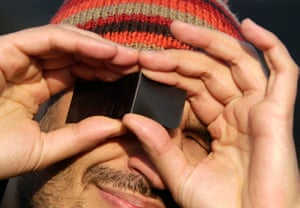 eclipse: A man looks at a partial solar eclipse over Romania, Bucharest