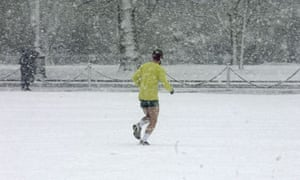 A man out jogging after a heavy snow fall in London