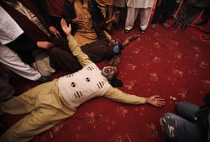 Salman Taseer Funeral: Pakistani mourners lay on the ground crying during the funeral procession
