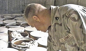 A US soldier inspects barrels of explosives, 2003.
