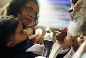 Orthodox Christmas: A child receives communion from a Coptic Orthodox priest