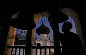 Orthodox Christmas: A bell ringer is silhouetted as he stands at the tower of a cathedral