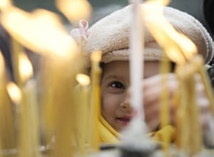 Orthodox Christmas: A girl lights candles during a Christmas liturgy in St. Clement Cathedral