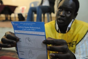 Sudan referendum: An official shows a ballot paper to a South Sudanese man living in Kenya