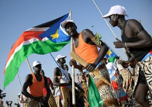 Sudan referendum: A group of southern Sudanese men wave local flags and dance