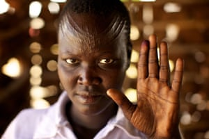 Sudan voters: Rebecca Sanie holds up her ink-stained finger to show she voted