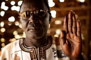 Sudan voters: Chief Michael Aburi holds up his ink-stained finger to show he voted