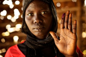 Sudan voters: Hellena Akwat holds up her ink-stained finger to show she voted