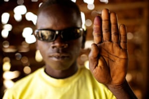 Sudan voters: Sapana Lapai Fresser holds up his ink-stained finger to show he voted
