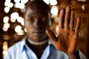 Sudan voters: Richard Wanu holds up his ink-stained finger to show he voted