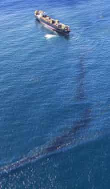 Oil streams from the Rena stuck on Astrolabe Reef in New Zealand's Bay of Plenty
