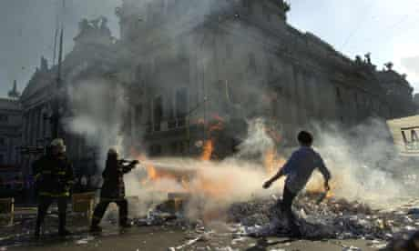 Firefighters put out a fire set by anti-government demonstrators in Buenos Aires, December 2001
