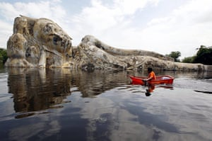 Flooding in Thailand: A resident rows a boat past a submerged Buddha statue