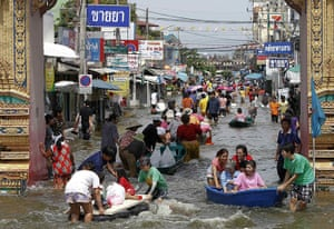 Flooding in Thailand: People make their way through a flooded street