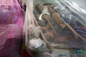 Flooding in Thailand: People rest under mosquito nets at a makeshift evacuation centre