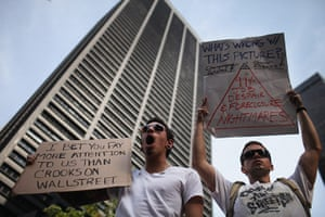 Occupy protests: New York:  Wall Street protesters hold up signs at Zuccotti Park
