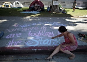 Occupy protests: Los Angeles: A woman writes messages in chalk at Occupy LA protest camp