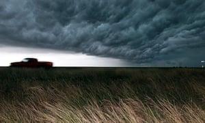 car drives under dark clouds