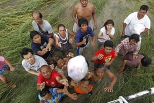 Thailand floods: Residents catch relief goods distributed from a helicopter in Ayutthaya