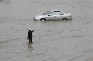 Thailand floods: A traffic policeman gestures to a car along a flooded stree, Thailand