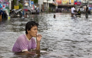 Thailand floods: A man smokes a cigarette as he sits in the flooded streets, Thailand