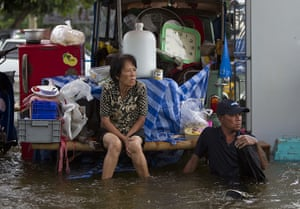 Thailand floods: People sit amongst their belongings in water in Ayutthaya