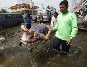 Thailand floods: A rescue worker evacuates a woman from a flooded area in Pathum Thani