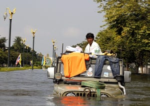 Thailand floods: A Thai resident sits on a flood-submerged jeep on a street in Ayutthaya